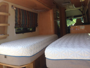 A RV with a his and hers sleeping arrangement